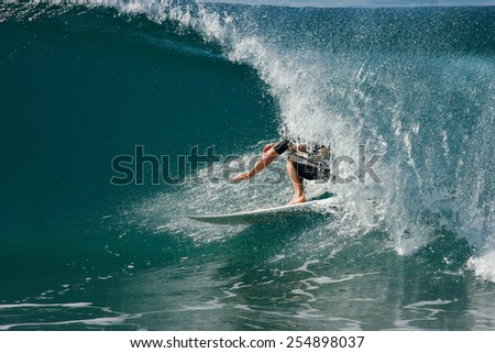 A surfer rides a tube on a beautiful, blue wave in the ocean.