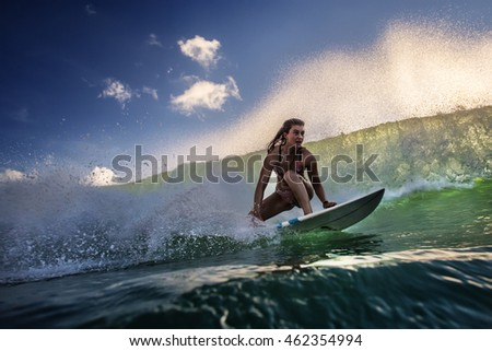 A surfer riding inside an ocean green wave lit with sunset light. Watersport Activity in Indonesian island Bali. Green water with blue clear sky.