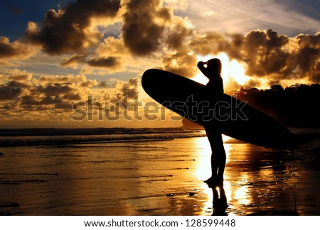 A surfer scopes out the waves during a sunset. - stock photo