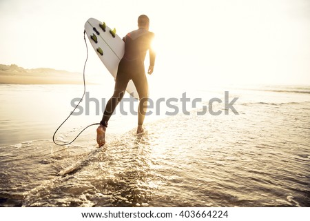 A surfer with his surfboard running to the waves - stock photo