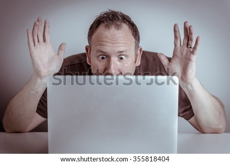 A surprised man with hands in the air sits hidden behind a laptop notebook computer staring at the screen with wide eyes and a shocked or frustrated expression on his face. - stock photo