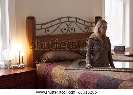 A surreal, altered photo of a girl standing inside a mirror placed on a bed. - stock photo