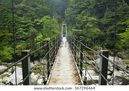 A suspension bridge crossing a river in lush rainforest on the southern island of Yakushima, Japan. - stock photo