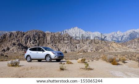 A SUV at Rocky desert in Eastern Sierra, California. - stock photo