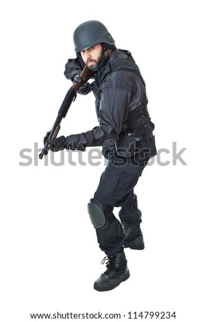 a swat agent wearing a bulletproof vest and aiming with a gun - stock photo