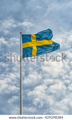 A Swedish flag waving in the wind against a beautiful summer sky.