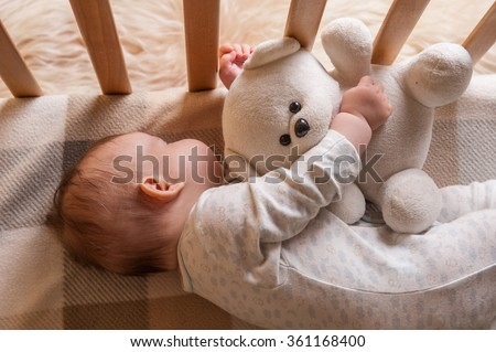 a sweet baby sleeping on a blanket with a bear - stock photo