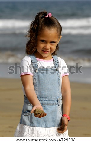 A sweet happy child on a beach playing with sand.