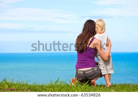 A sweet image of a a young mother and child looking at a beautiful ocean view together