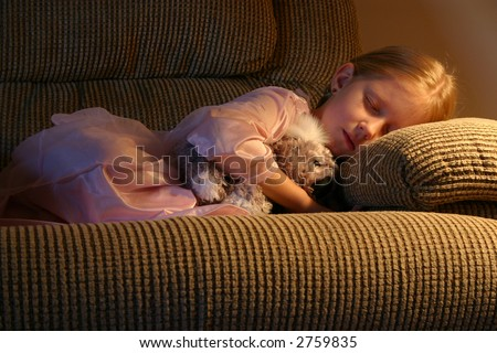 A sweet little girl fast asleep in a comfy chair under the soft glow of a lamp with her favorite cuddle toy. - stock photo