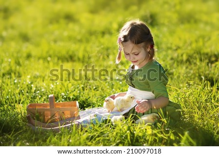 A sweet little girl in a green dress sitting with chicks on the bright grass in a sunny summer day. Kids and nature  - stock photo