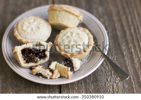 A sweet mince pie, a traditional rich festive food, on a plate with a fork on wooden background. - stock photo