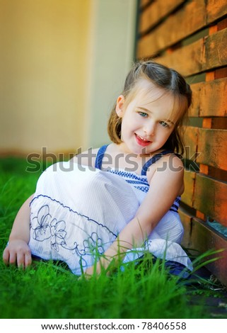 A sweet 4 year old is looking happily at the camera.  She is leaning against a red timber wall.  She looks relaxed and happy. - stock photo