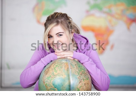 A sweet young cheerful schoolgirl with a globe in geography class. - stock photo