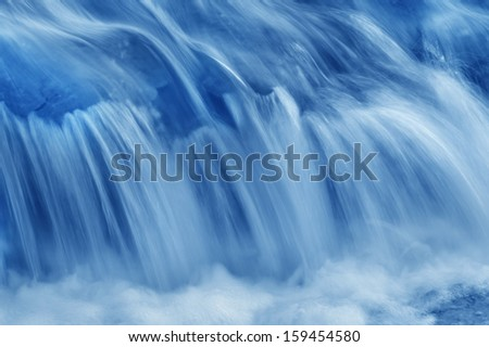 A swiftly moving stream in shades of blue. - stock photo