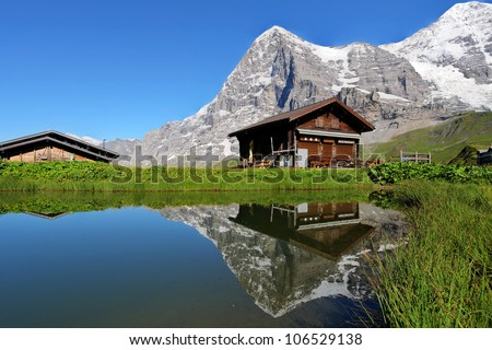 A swiss mountain chalet reflecting in a calm pond with the iconic north face of Eiger Mountain in the Bernese Alps, Switzerland. - stock photo