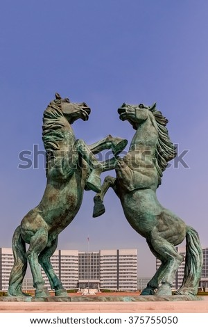 A symbol of strength and invincibility: Horses play a major role in Mongolian culture. Here they dominate the central square of new Ordos City, Inner Mongolia. - stock photo