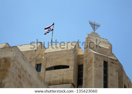 A synagogue in the Jewish Quarter of the old city of Jerusalem, with an Israel flag and a Hannukah Menorah on its roof. - stock photo
