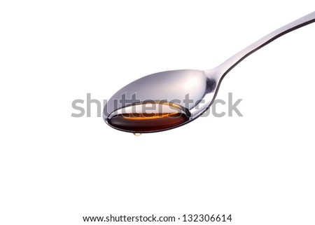 a syrup liquid pours off of a metal spoon