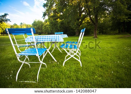 a table and some empty chairs on a green meadow in summer, ready for picnic