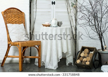 A table covered with thick cloth with a cup of tea and tea and marshmallow in a wicker plate. Tea Party. Design veranda with a chair with a pillow and firewood - stock photo