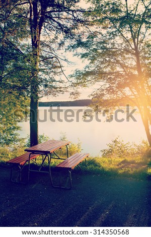 A table set by the beach in Finland. People can enjoy their snacks by the lake while traveling with their cars on holiday. Image has a vintage effect applied.