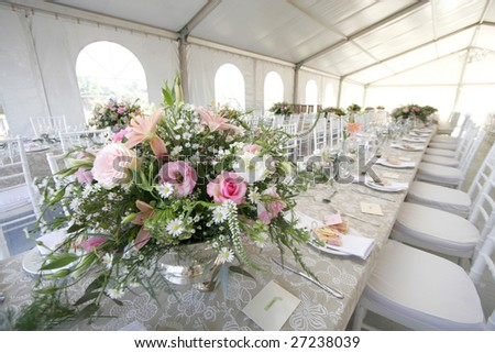 A table setup for a wedding reception in a big tent