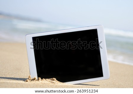 a tablet computer with a black blank space in the screen, in the sand of a beach - stock photo