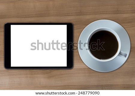 A tablet computer with a white screen and a cup of coffee on a wooden desktop - stock photo
