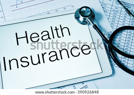 a tablet computer with the text health insurance written in its screen and a stethoscope on a table full of charts and spreadsheets - stock photo