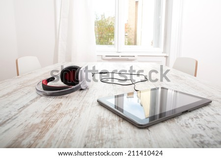 A Tablet PC with headphones on the Table. - stock photo
