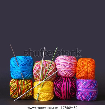 A tack of colorful yarn coils and needles over grey background - stock photo