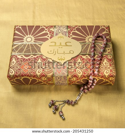 A tag with 'Eid Mubarak' message in arabic script on a golden gift box along with islamic rosary - stock photo