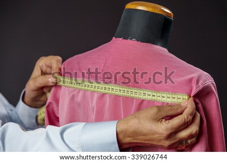 A tailor takes measures of a shirt on a fashion mannequin  - stock photo