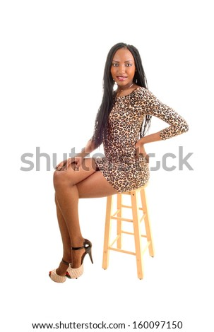 A tall black woman in a brown short dress sitting on a chair with her long braid hair for white background.  - stock photo