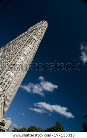A tall building with many windows next to some trees. - stock photo