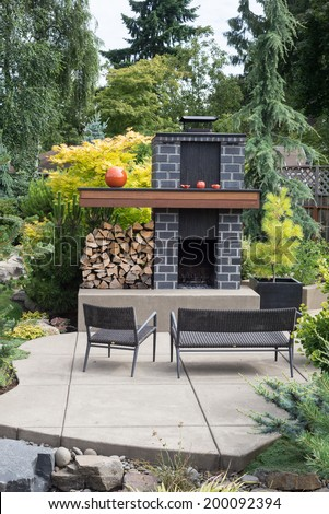 A tall, custom-designed fireplace with grey bricks and plenty of firewood sits on an inviting patio in a Pacific Northwest back yard. - stock photo