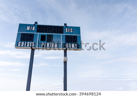 A tall electronic scoreboard at a local soccer cum football field against a blue sky with copy space. - stock photo