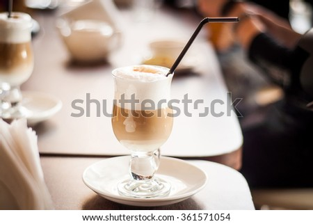 A tall glass containing latte coffee standing on a wooden table in cafe - stock photo