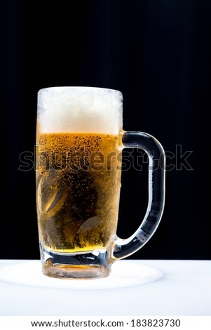 A tall glass of beer topped with foam against a black background. - stock photo