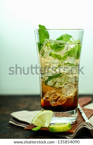 A tall glass of ice cold mujito rum cocktail with mint leaves and lime standing on a folded napkin and coaster on a wooden counter in a bar or club