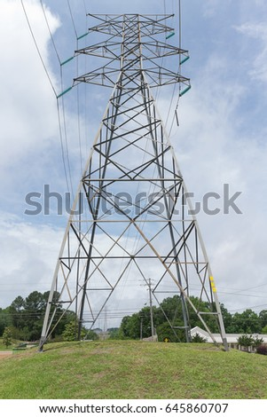 A tall, high voltage, electrical pylon on the hill.
