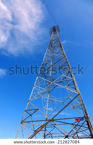 A tall high voltage electricity power mast against a blue sky - stock photo