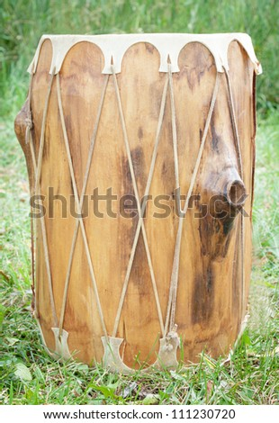 A tall Indian drum placed in the grass - stock photo