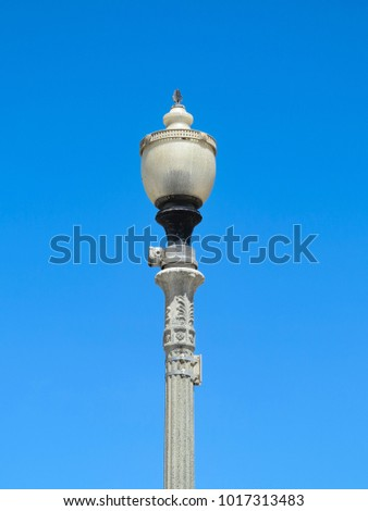A tall lamp post with blue sky behind
