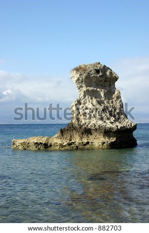 A tall rock on the sea.