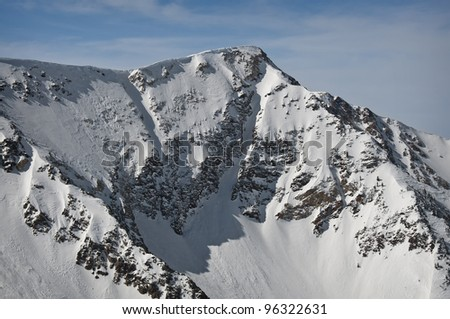 A Tall Rocky Mountain with Fresh New Snow - stock photo