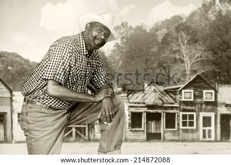 A tall, senior black cowboy in an old western town.  Sepia Toned - stock photo