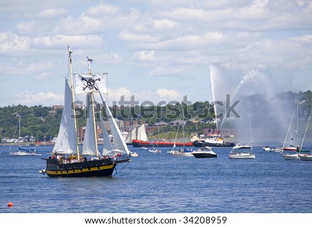 A tall ship is saluted with water cannons as she sails out of Halifax Harbour with Dartmouth in the background during the sail past of the Nova Scotia Tall Ships Festival 2009. - stock photo