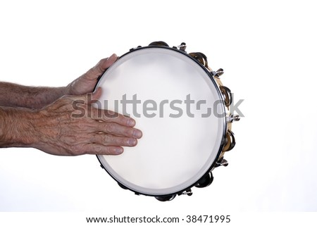 A tambourine being played by a man?s hands isolated against a white background. - stock photo